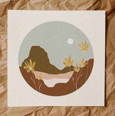 An evening desertscape. with mustard yellow flowers in the foreground, taup, brown and peach mountains behind them and a pale blue, speckled sky and white moon. Image is in a circle shape with white border on square print