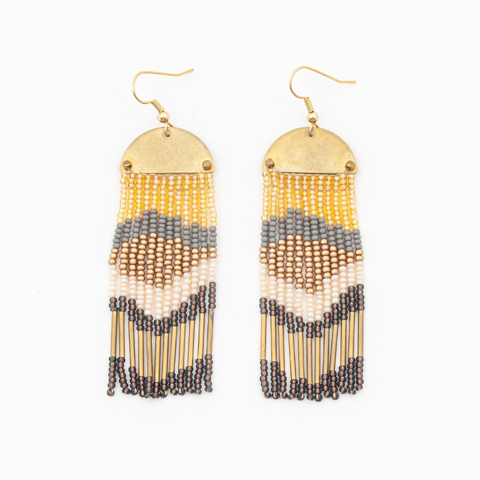 earrings with a hook, brass half moon  with curved side facing up and descending fringe in colorful layer: gold, grey, bronze, cream, a dark grey/blue color and long gold beads forming an abstract design in the beading