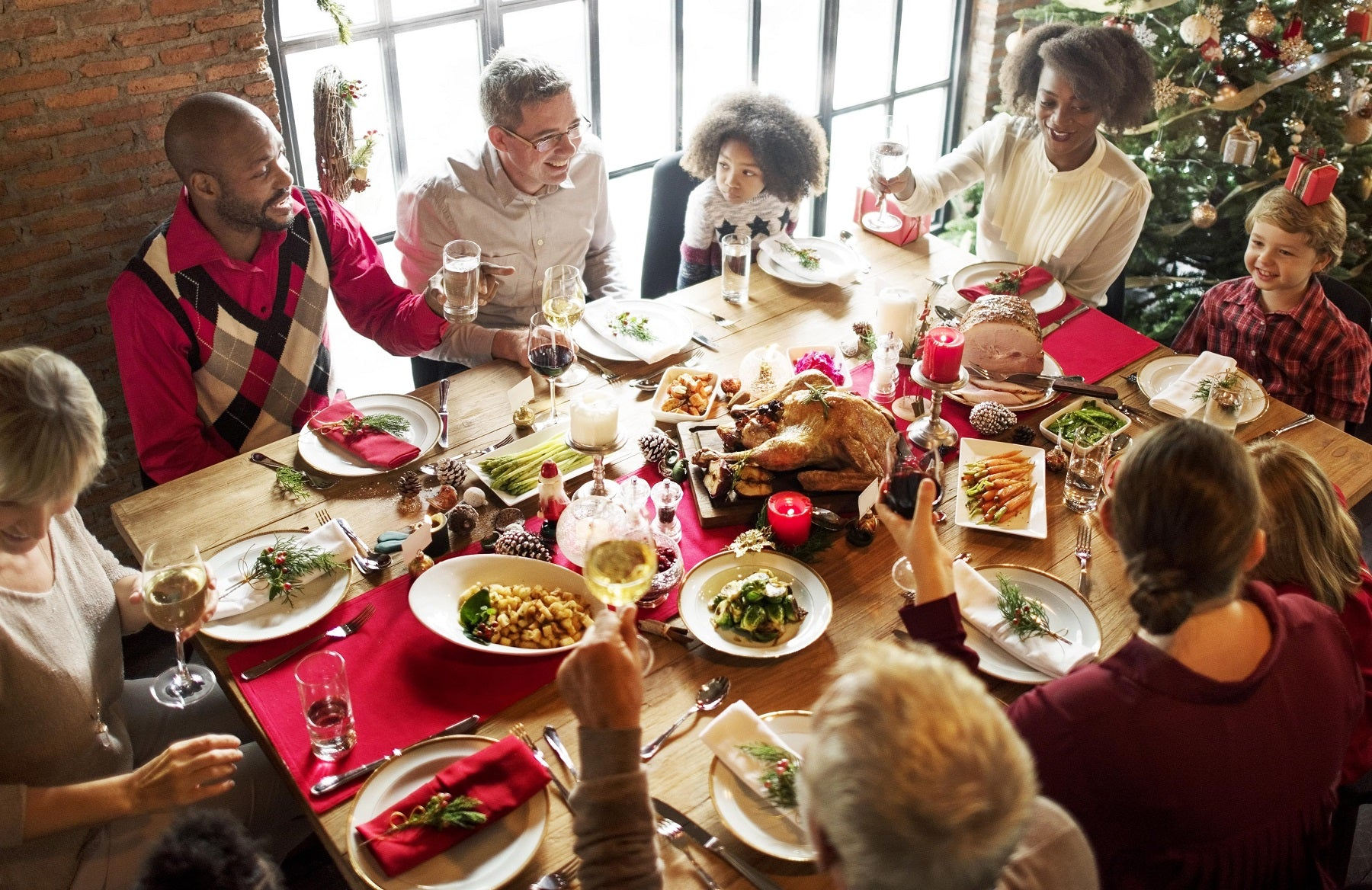 A family sitting around a table full of food during a Christmas dinner