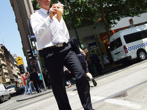 A business man walking across the road holding a folder