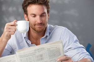 A man holding a cup of coffee reading a newspaper