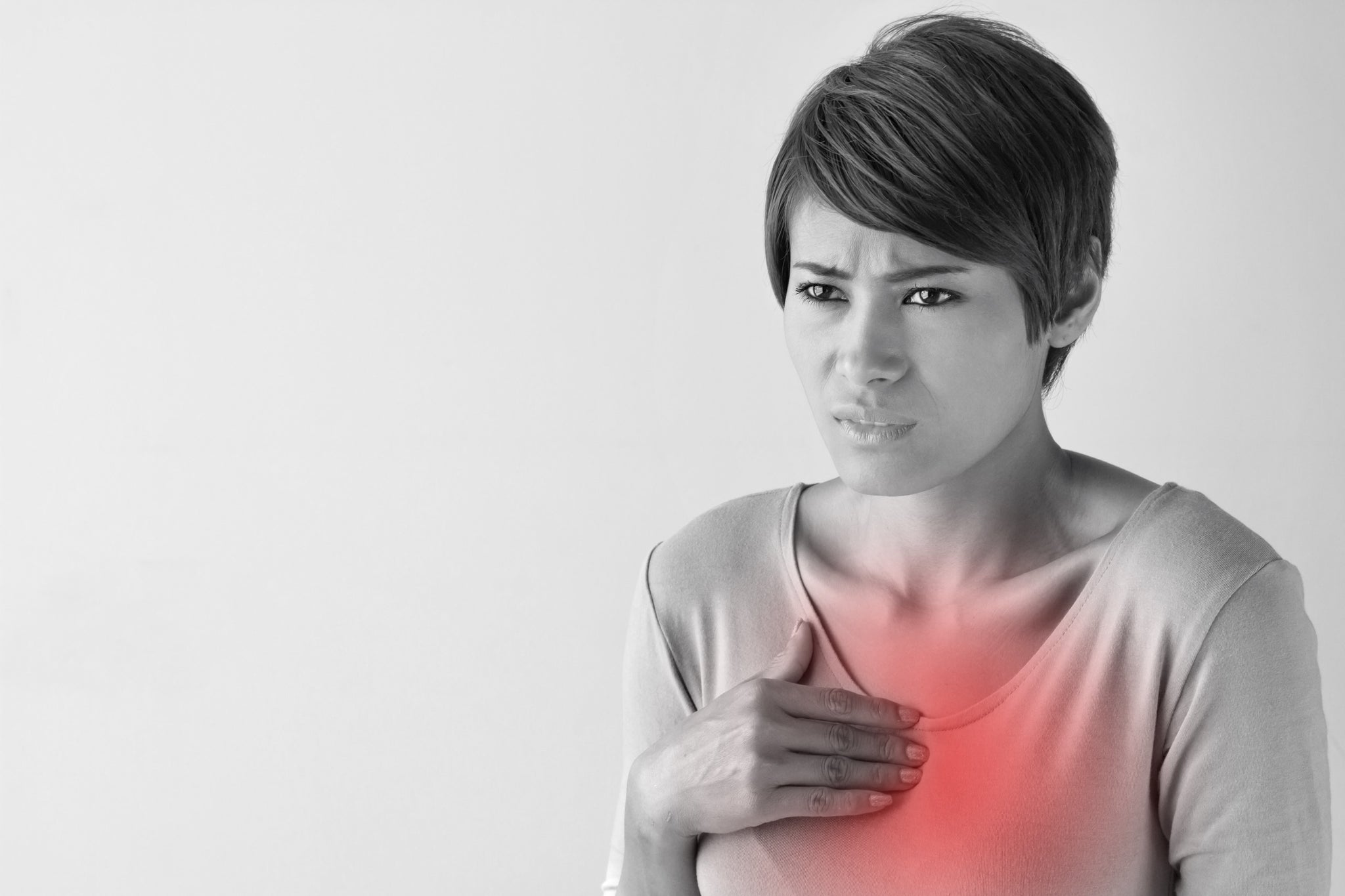 A woman with her hand placed on her chest in pain