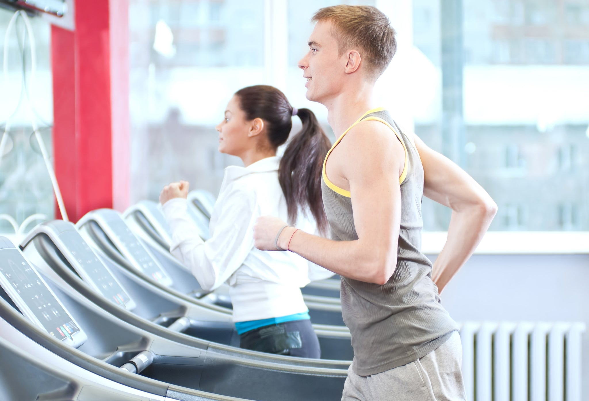 A woman and a man running on a treadmill