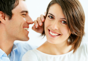 A man whispering into a woman's ear who looks very happy