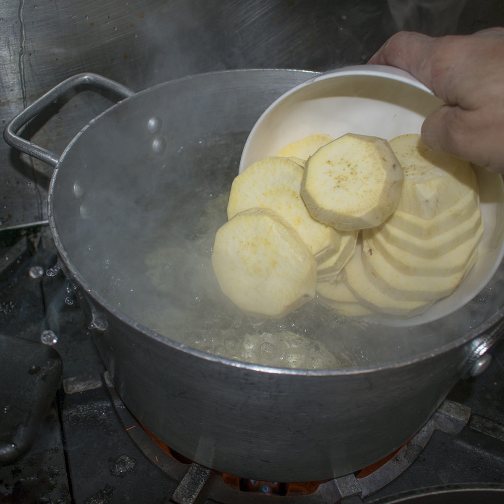 """Peel and slice the potatoes into 1/4"""" rounds and boil them in salted water for 5-8 minutes"""