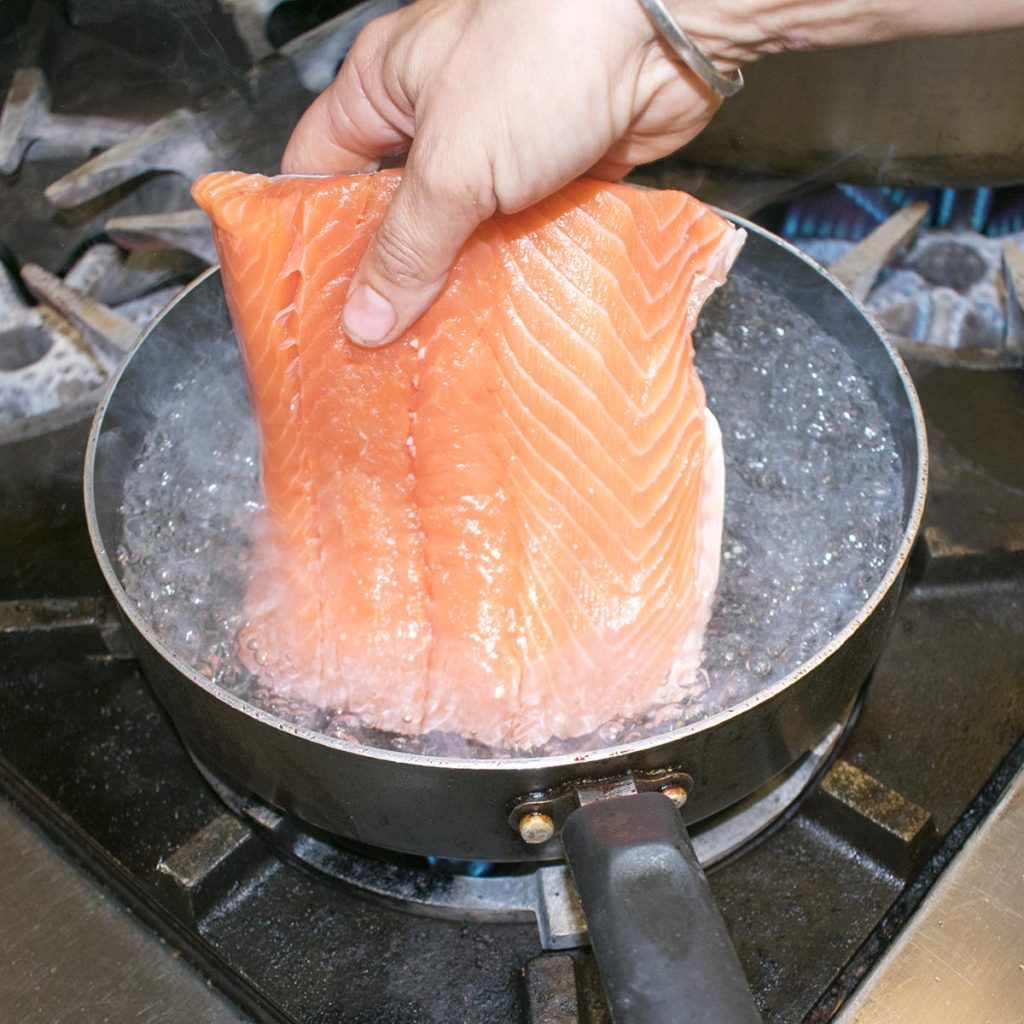 Gently lower the skinless aip salmon filet into 2 inches of simmering water.
