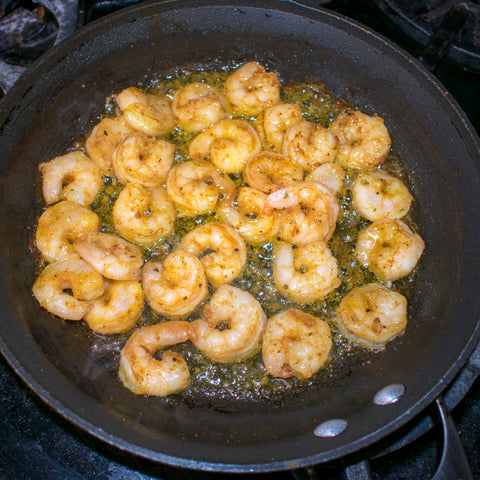 aip rub on shrimp being grilled in skillet