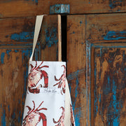 crab print apron hanging over cupboard door - close up