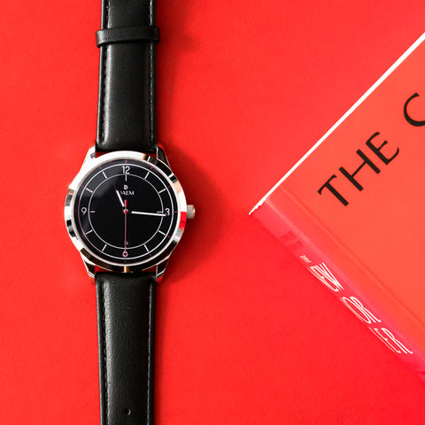 DAEM midnight watch next to New Yorker book