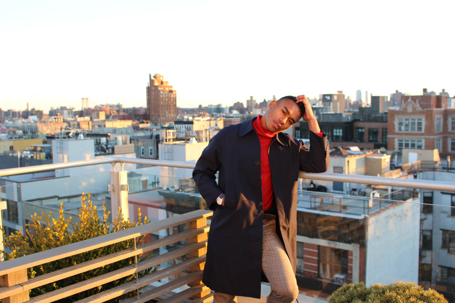 Man in blue coat on sunset rooftop wearing DAEM watch