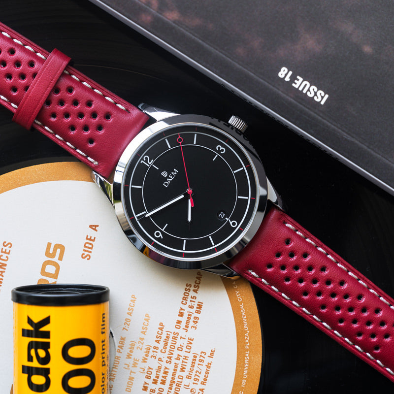 DAEM Nassau black dial red perforated strap watch
