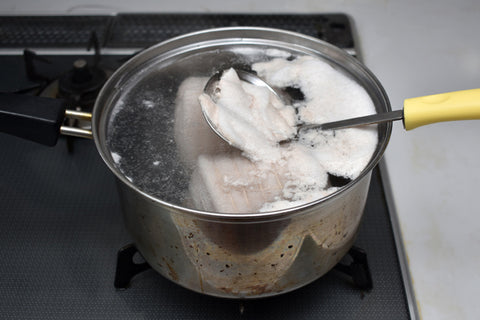 Skimming froth from pork chashu boil