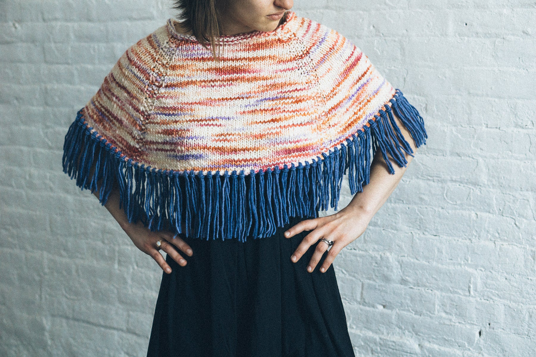 Knitted poncho with fringe made from handspun yarn in aran weight.