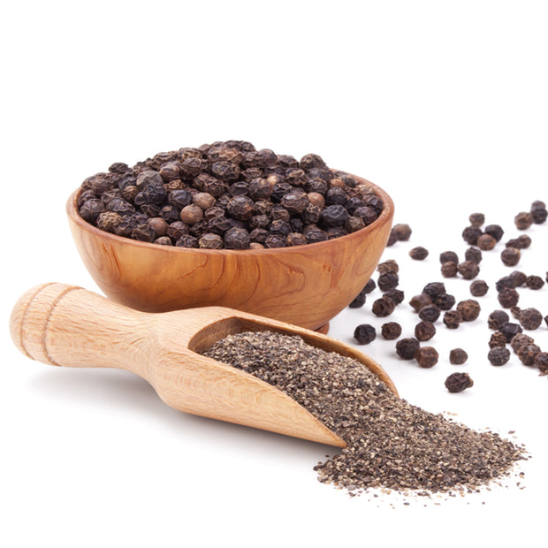 whole black pepper and ground pepper in spoon and bowl