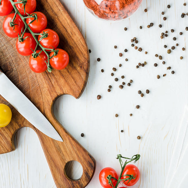 black pepper on tomatoes on cutting board