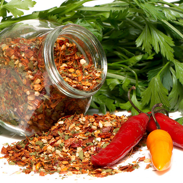 cajun spice blend in jar with peppers and greenery in the back