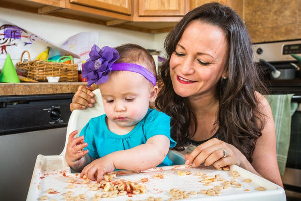 Baby with Mom Playing with Cereal