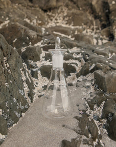 Theodore Afrika - Still Symmetry 01 - Image of a clear vase between rocks on the beach