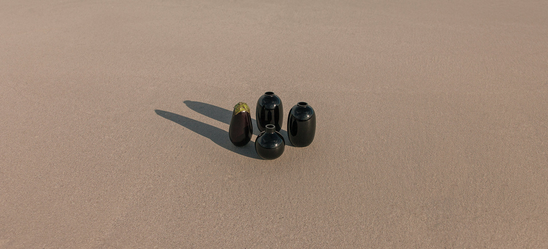 Theodore Afrika - Still Symmetry 03 - Image of various black vases and an eggplant on a beach.