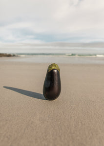 Theodore Afrika - Still Symmetry 04 - Print of an eggplant on the beach.