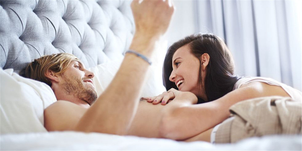 man and woman talking on the bed