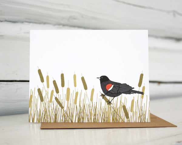 A greeting card showing a hand-drawn illustration of red-winged blackbird resting amongst a swath of cattails. Shown standing on a Kraft paper envelope in front of a white-washed log wall.