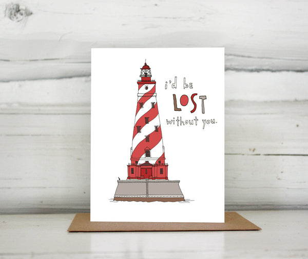 "A greeting card showing a hand-drawn illustration of the White Shoals lighthouse in Michigan, a red and white striped lighthouse. The card has a hand-lettered message reading, ""I'd be lost without you."" Shown standing on a Kraft paper envelope in front of a white-washed log wall."