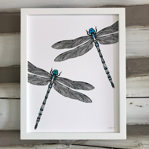 A print of a hand-drawn ink illustration of two dragonflies, one with blue highlights and one with teal accents. Shown in a white frame against a whitewashed log wall.