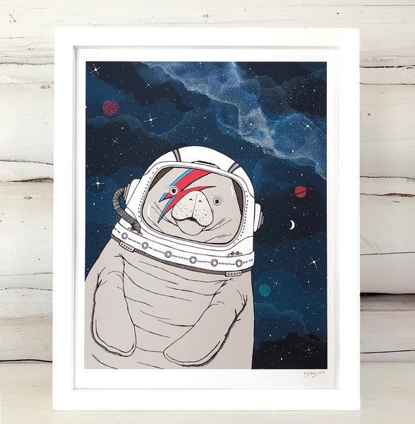 A framed print of a hand-drawn illustration of a manatee floating in space, wearing an astronaut's helmet with a red and blue lightning bolt over one eye like the iconic image of David Bowie, ganging on a white log wall.