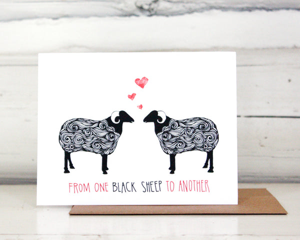 "A greeting card with a hand-drawn ink illustration of a pair of black and white sheep with horns facing each other with three hearts over their heads. A hand-lettered message reads, ""From one black sheep to another."" Shown standing on a Kraft paper envelope in front of a white-washed log wall."