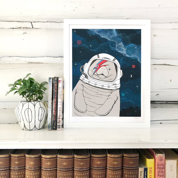 A print of a hand-drawn illustration of a manatee floating in space, wearing an astronaut's helmet with a red and blue lightning bolt over one eye like the iconic image of David Bowie on his Aladdin Sane album cover. Seen in a white frame on a book shelf with a plant and in front of white log walls.