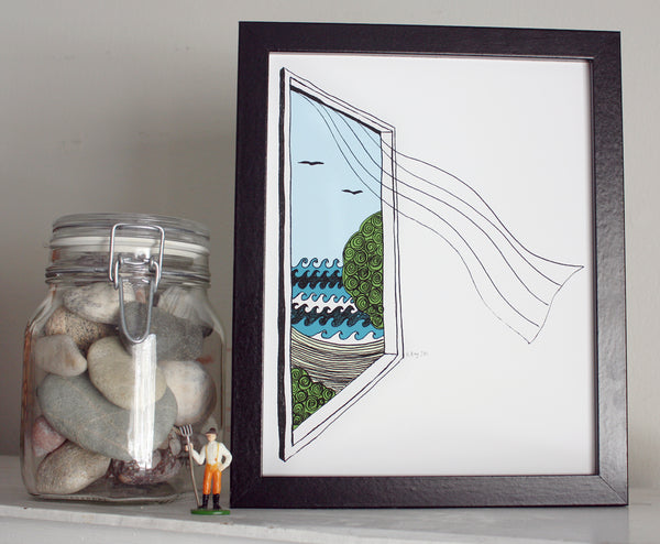 A print of a hand-drawn illustration of a window looking out on ocean waves, a beach and seagulls, a sheer curtain blows in from the window. Shown in a black frame next to a jar of rocks.