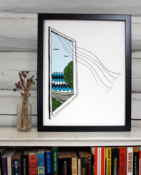 A print of a hand-drawn illustration of a window looking out on ocean waves, a beach and seagulls, a sheer curtain blows in from the window. Shown in a black frame on top of a bookcase in front of a whitewashed log wall.