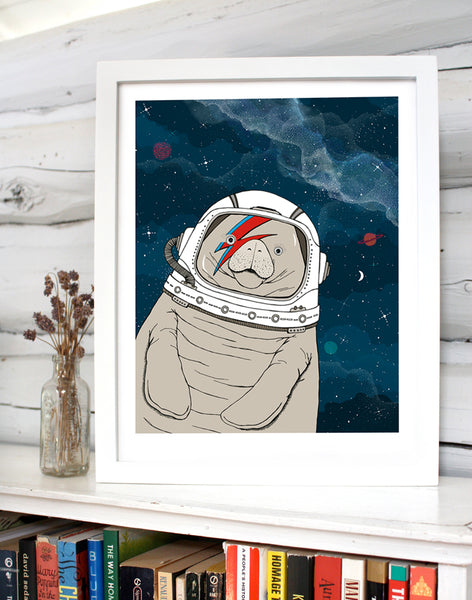 A print of a hand-drawn illustration of a manatee floating in space, wearing an astronaut's helmet with a red and blue lightning bolt over one eye like the iconic image of David Bowie on his Aladdin Sane album cover. Seen in a white frame on a book shelf in front of white log walls.