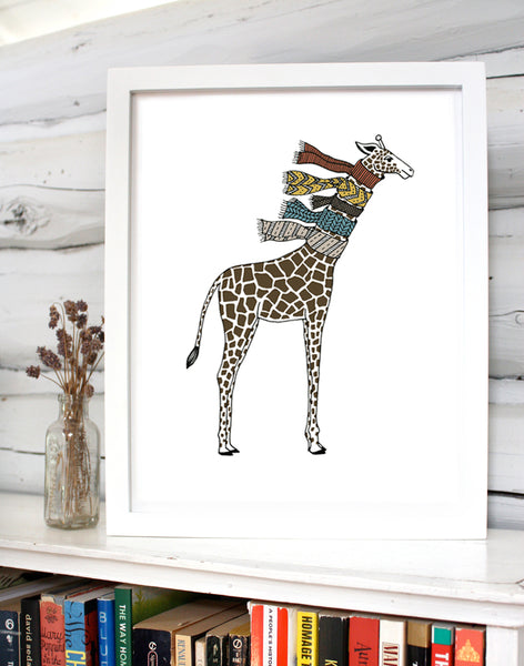 A print of a hand-drawn illustration of giraffe wearing five knit scarves on its neck. Shown in a white frame on top of a bookcase with a small vase of flowers in front of a whitewashed log wall.