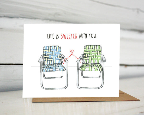 "A greeting card showing a hand-drawn illustration of a pair of old-fashioned lawn chairs with webbing and metal frames, one in blues and one in greens. A red thread ties the two chairs together and forms a small heart shape between them. A hand-lettered message reads, ""Life is sweeter with you."" Shown standing on a Kraft paper envelope in front of a white-washed log wall."