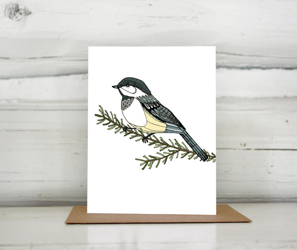A greeting card with a hand-drawn ink illustration of a chickadee resting on a branch. Shown standing on a Kraft paper envelope in front of a white-washed log wall.