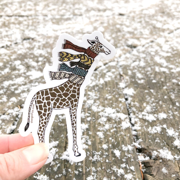 A hand holding up an illustrated vinyl sticker of a hand-drawn giraffe wearing five knit scarves on its neck in front of a wood deck covered with little bits of snow.