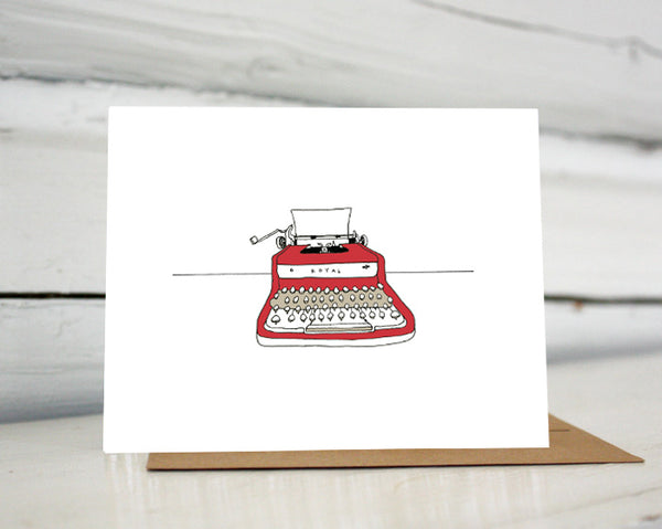 A greeting card showing a hand-drawn illustration of red Royal vintage typewriter with a piece of blank paper loaded in it. Shown standing on a Kraft paper envelope in front of a white-washed log wall.