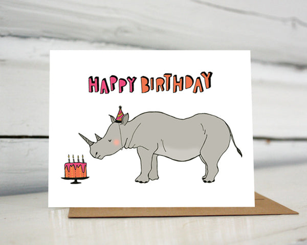 "A greeting card showing a hand-drawn illustration of a rhinoceros wearing a pink and black striped party hat that matches stripes on his horns, looking at an orange and pink birthday cake. A hand-lettered message reads, ""Happy Birthday."" Shown standing on a Kraft paper envelope in front of a white-washed log wall."