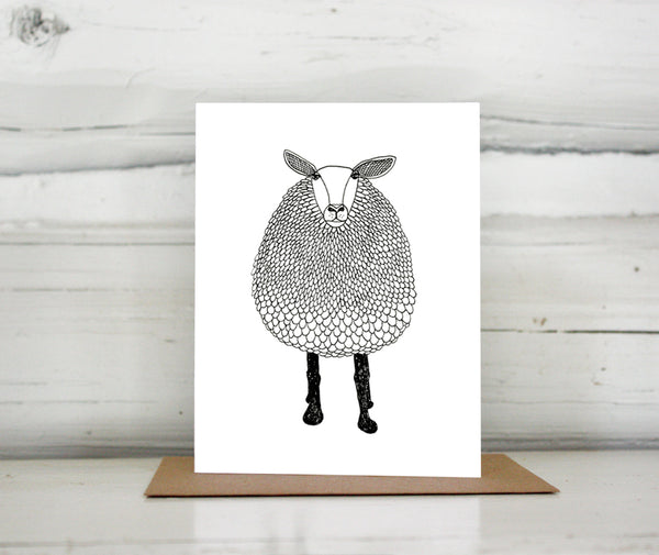 A greeting card with a hand-drawn black and white ink illustration of a sheep. Shown standing on a Kraft paper envelope in front of a white-washed log wall.