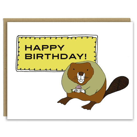 "A greeting card with a hand-drawn illustration of a rotund beaver wearing an olive green sweater and holding a cupcake with a pink swirl of frosting standing in front of a sign that reads, "" Happy Birthday!"" Shown with a Kraft paper envelope on a white background."