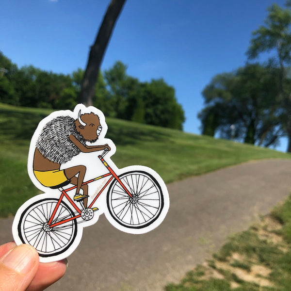 A hand holds a vinyl sticker with a hand-drawn ink illustration of a bison riding a red bicycle, wearing yellow cycling shorts and yellow sneakers, seen riding along a paved path with grass and trees in the background.
