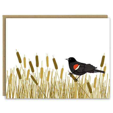 A greeting card showing a hand-drawn illustration of red-winged blackbird resting amongst a swath of cattails. Shown with a Kraft paper envelope on a white background.
