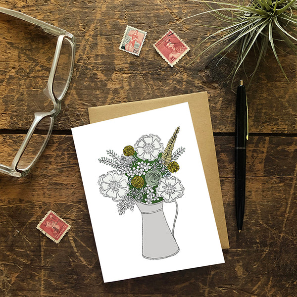 A greeting card showing a hand-drawn illustration of a bouquet of flowers in greys, greens and golds in a silver metal pitcher. Shown with a Kraft paper envelope on a worn wooden surface with reading glasses, stamps, a pen and an air plant.