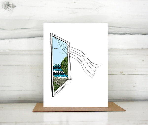 A greeting card showing a hand-drawn illustration of a window looking out on ocean waves, a beach and seagulls, a sheer curtain blows in from the window. Shown standing on a Kraft paper envelope in front of a white-washed log wall.
