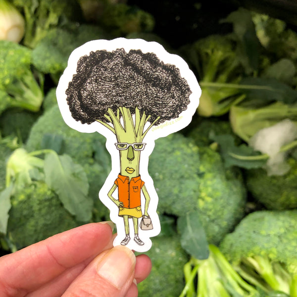 A hand holding a sticker with a hand-drawn ink illustration of a broccoli woman with one hand on her hip, wearing glasses, an orange shirt, yellow skirt and white sneakers, carrying a purse, in front of bunches of real broccoli in the grocery store.