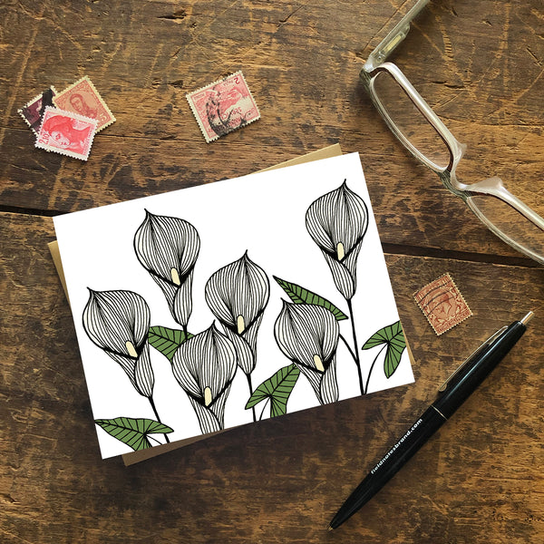 A greeting card with a hand-drawn ink illustration of six pale yellow calla lilies. Shown with a Kraft paper envelope on a worn wooden surface with reading glasses, stamps and a pen.