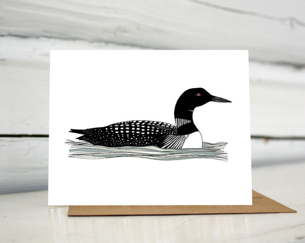 A greeting card showing a hand-drawn illustration of a black and white loon with its signature red eye, floating gently on the waves. Shown standing on a Kraft paper envelope in front of a white-washed log wall.