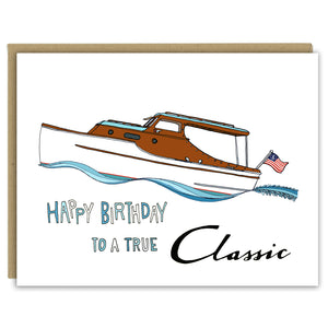 "A greeting card with a hand-drawn illustration of a classic Christ Craft boat riding high in the waves with an American flag flying on the stern. A hand-lettered message reads, ""Happy Birthday to a true Classic."" Shown with a Kraft paper envelope on a white background."